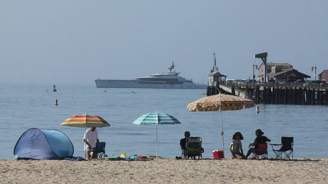 Early beachgoers secure spots on the shore at Santa Barbara, Calif., on Sunday, as the superyacht Bravo Eugenia lies offshore. Californians packed beaches, lakes and recreation areas Sunday to seek relief from a record heat wave that strained the electricity grid and threatened to trigger a third round of rolling power outages.