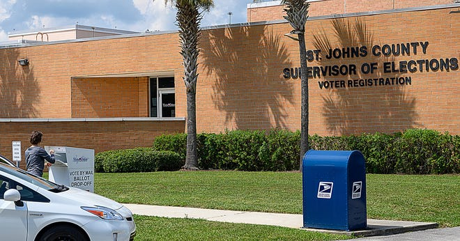 A voter drops off a vote by mail ballot in a box in front of the St. Johns County Supervisor of Elections office in St. Augustine on Monday.