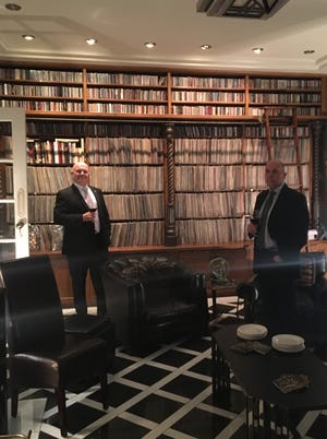 Barry Gordon, left, owner of MaxSold, an online downsizing auction company, stands before a client's vast music collection of record albums and CDs. [Photo courtesy of MaxSold]