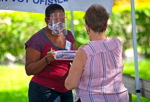 A polling worker helps a citizen check in during early voting for the primary election at Miami Lakes Community Center in Hialeah on Thursday. [David Santiago / Miami Herald via AP]