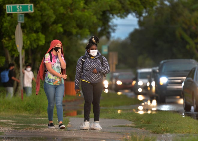 Southeast High School freshmen Jaylei Gimbel, left, and Aisha King walk to school on the first day of class for students in Manatee County on Aug. 17, 2020.