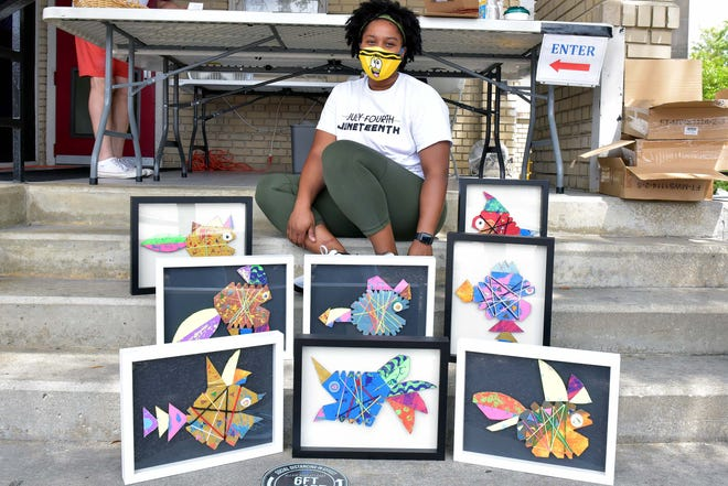 Ashley T. Thompson, a visual arts teacher at Walker-Spivey Elementary School, shows off artwork that her students created for submission to the Arts Council of Fayetteville-Cumberland County's 'Public Works' exhibit on Aug. 15. [Ed Clemente for The Fayetteville Observer]