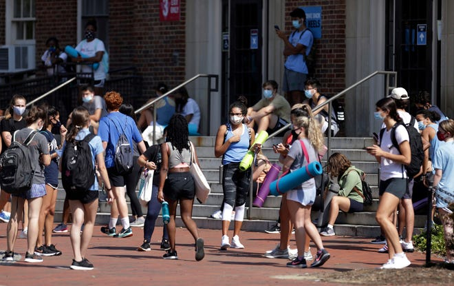 University of North Carolina students wait outside Woolen Gym on the Chapel Hill campus to enter for a fitness class Monday. The university announced minutes before that all classes will be moved online starting Wednesday because of COVID-19 clusters on campus. [Julia Wall/The News & Observer via AP]