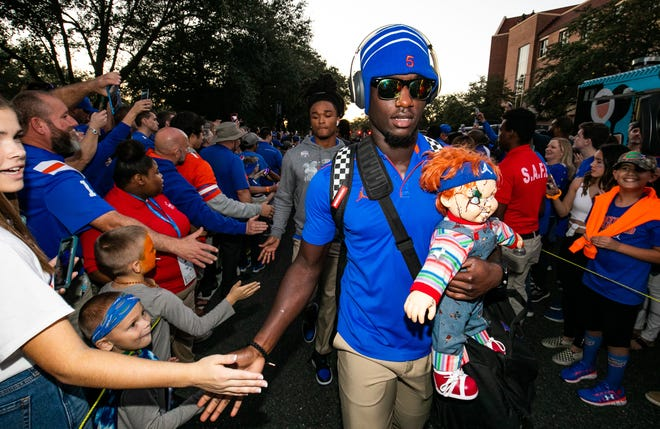 Florida defensive back Kaiir Elam gives low-fives to fans as he carried the Chucky doll during Gator Walk on Nov. 30, 2019 at Ben Hill Griffin Stadium. [Doug Engle/Gainesville Sun]