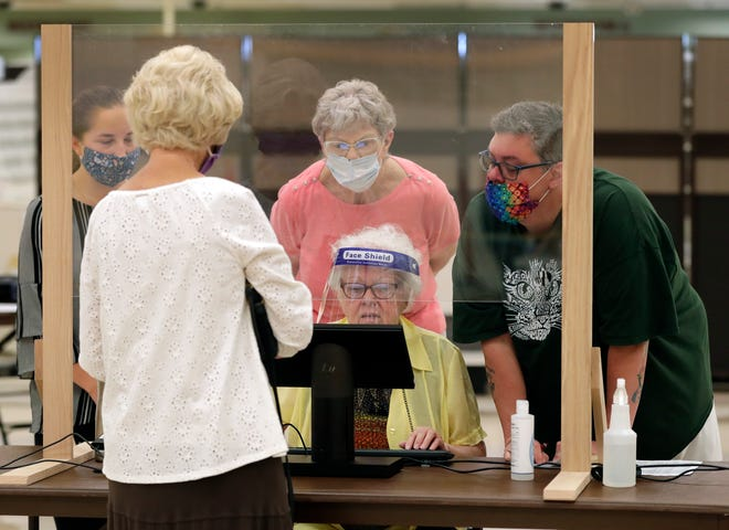Poll workers help a resident register to vote in August at the former Shopko store in Neenah.