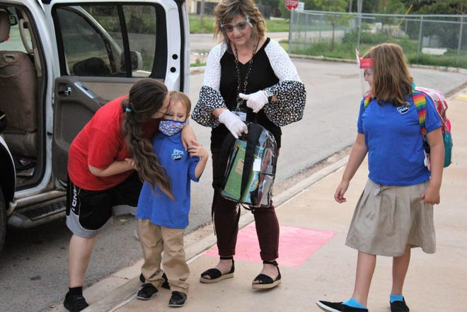 Audrey Moss gives her son Eden, a kindergartener a kiss goodbye while his sister Aeris, a fourth-grader watches. With them is art teacher Cassie Irwin. It was the first day of school Monday at Texas Leadership Charter Academy.