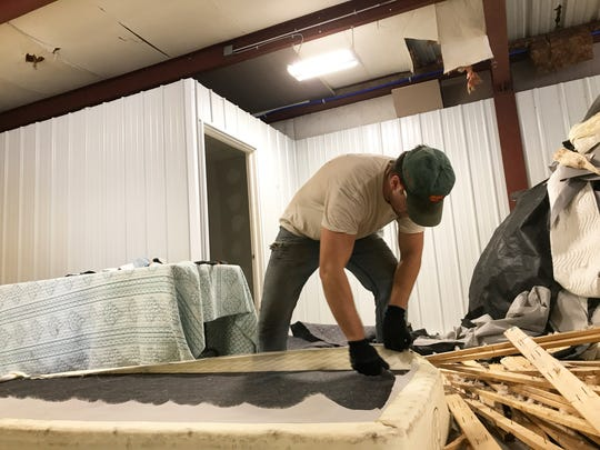 Cameron Costa, 20, cuts a fabric cover from a mattress he is disassembling at Sleep Well Recycling in Burlington on Aug. 17, 2020.