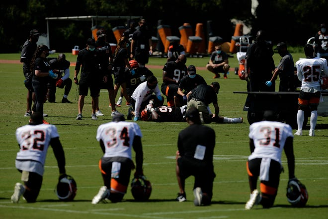Cincinnati Bengals defensive tackle Renell Wren (95) is examined by the training staff before being carter off with a leg injury during training camp at the Paul Brown Stadium practice field in downtown Cincinnati on Monday, Aug. 17, 2020.