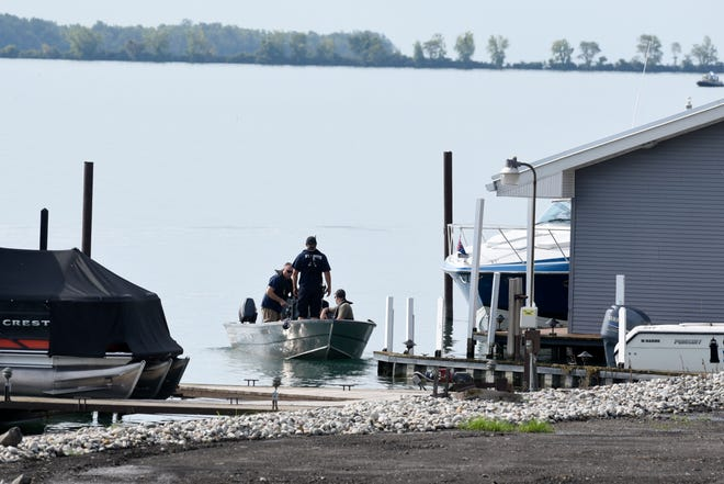 Authorities search for two men who are missing after a boat capsized near Stoney Island in the Detroit River on the east side of Grosse Ile, Monday, August 17, 2020. The boat capsized Sunday night with at least 9 people aboard.