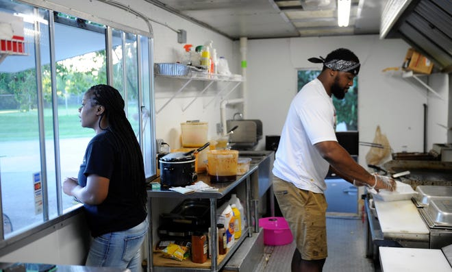 Tirita and Bryson Hatchett work in the Trappin' Chick'n food truck on Thursday, Aug. 20, 2020.