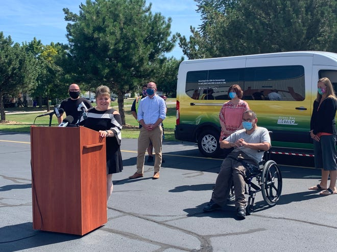 Patricia Kiewiz, transit director for Green Bay Metro, announces the new GB On-Demand app and ride-sharing service on Monday, Aug. 17 by Green Bay Metro at 901 University Ave. She stands in front of one of the ride-sharing vehicles.