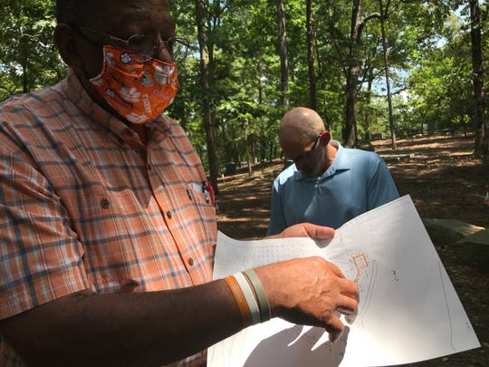 Dr. Jim Bostic, alum and volunteer who has been helping identify grave sites of enslaved people at woodland cemetery, points to a map, Aug. 17, 2020.