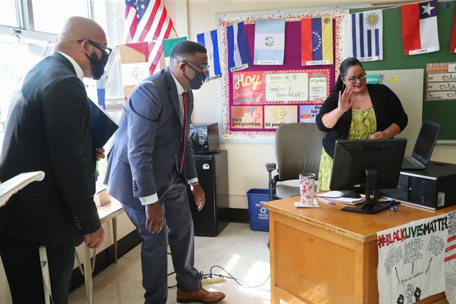 Milwaukee School of Languages teacher Marielle Rivera, right, greets her eighth-grade virtual Spanish class on the first day of school as Principal Juan Baez, left, and MPS Superintendent Keith Posley watch.
