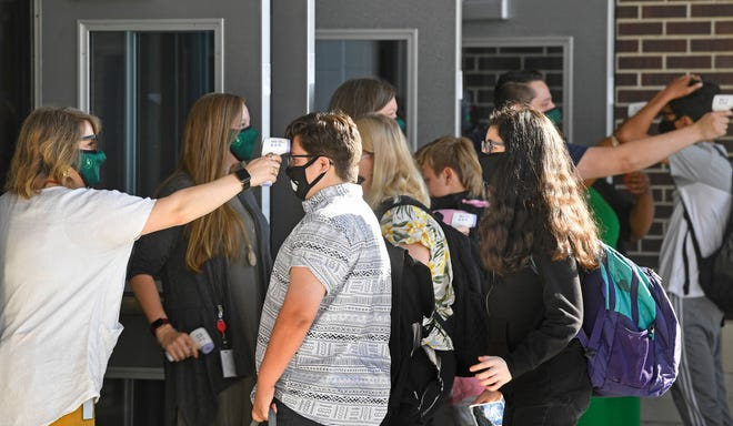 Students line up to have their temperatures checked Monday, Aug. 17, 2020, as Green Hill High students arrive for Wilson County Schools' first day of classes amid COVID-19 and after the March tornado in Mt. Juliet, Tenn.