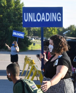 Lauren Strait helps with unloading as Stoner Creek Elementary students arrive at Mt. Juliet Middle School for Wilson County Schools' first day of classes Monday, Aug. 17, 2020 , amid COVID-19 and after the March tornado in Mt. Juliet, Tenn.