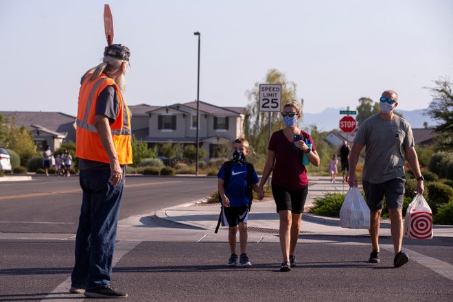 Harry White stops traffic as Shana and Bobby Seal walk with their son, Bentley, 7, on the first day of school on Aug. 17, 2020, at Faith Mather Sossaman Elementary School in Queen Creek. The Queen Creek Unified School District reopened all of its schools for in-person classes.