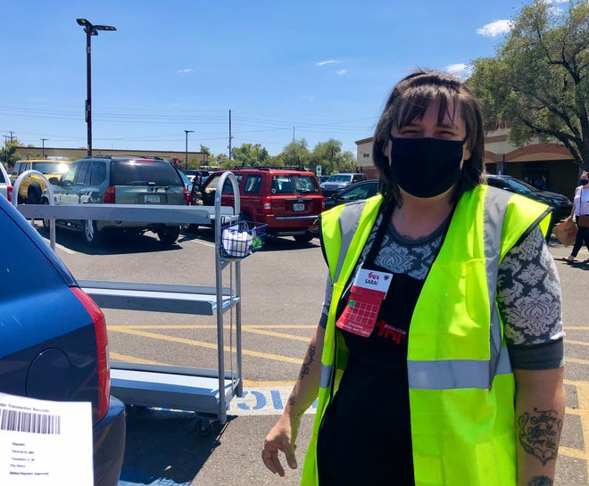 In my rear-view mirror, I saw a woman wearing a mask and yellow vest with a cart stacked with paper bags stop behind my car.