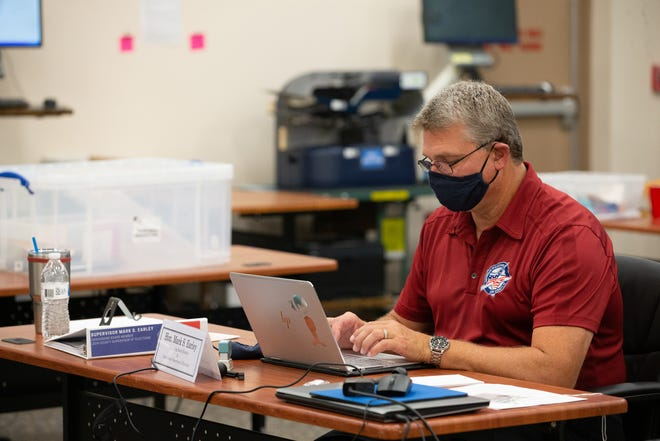 Leon County Supervisor of Elections Mark Earley works at his desk while canvassing workers open and sort vote-by-mail ballots before they are counted Monday, August 17, 2020.