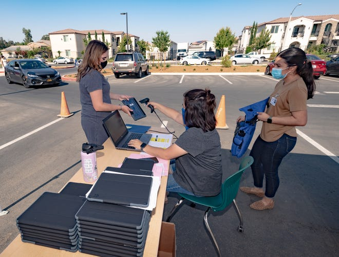 Aids Briana Baffo, left, Margaret McLain and Ashley Arias distribute iPads for preschoolers and remote learning at Sequoia High School on Monday, August 17, 2020.