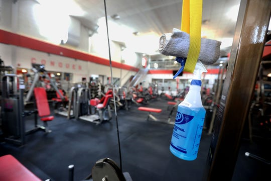 A bottle of sanitizer hangs from exercise equipment at Phoenix Fitness in Tuckahoe Aug. 17, 2020.  New York Gov. Andrew Cuomo announced that gyms will be able to re-open next Monday after ordering them closed in March due to the COVID-19 pandemic.