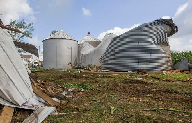 Residents begin cleaning up storm damage from dangerous straight-line winds and possible tornadoes caused by a rare derecho on Tuesday, Aug. 11, 2020.