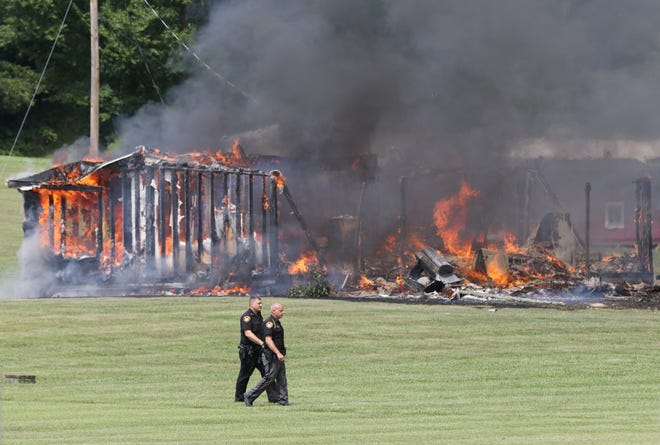 Two Muskingum County Sheriff's Office Deputies walk past a burning structure on Black Run Road on Monday.