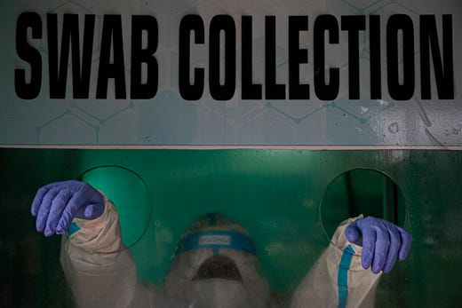 An Indian health worker waits to take a nasal swab sample to test for COVID-19 in a swab collection center in Gauhati, India, Aug. 17, 2020.