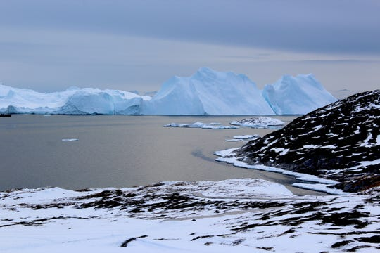 Icebergs near Greenland form from ice that has broken off from glaciers on the island. A new study shows that the glaciers are losing ice rapidly enough that, even if global warming were to stop, Greenland's glaciers would continue to shrink.