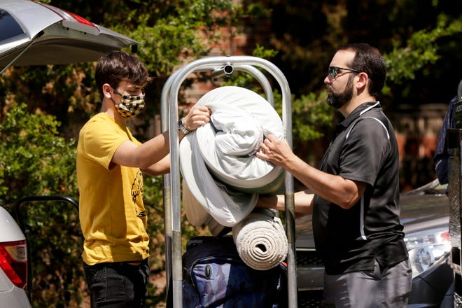 Evan Olinger of Sellersburg, Indiana, loads a cart with his dad, Scott Olinger, as Evan moves into his Purdue University dorm in August 2020.