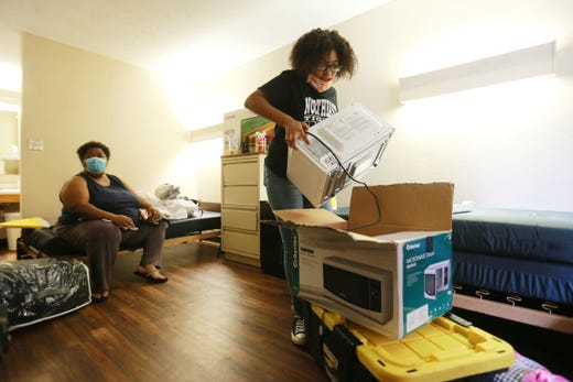 Ulyssa Howard, 19, of Corinth, Miss. unpacks her microwave and other items as she and her roommate begin moving into their dorm room at Woodd Hall at Northeast Mississippi Community College in Booneville, Miss., July 29, 2020.