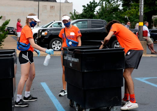 From left, St. Louis University students Miah Cramer, Alexis Schweitzer, and Adam Seger, members of Oriflamme, the student volunteer group which welcomes new students, clean the containers used by students moving in their belongings to the Reinert Hall dorm on a move-in day for SLU freshmen, Aug. 11, 2020. The containers are cleaned after each student uses it and the move-in days have been increased so that everyone can better abide by the social distancing guidelines.