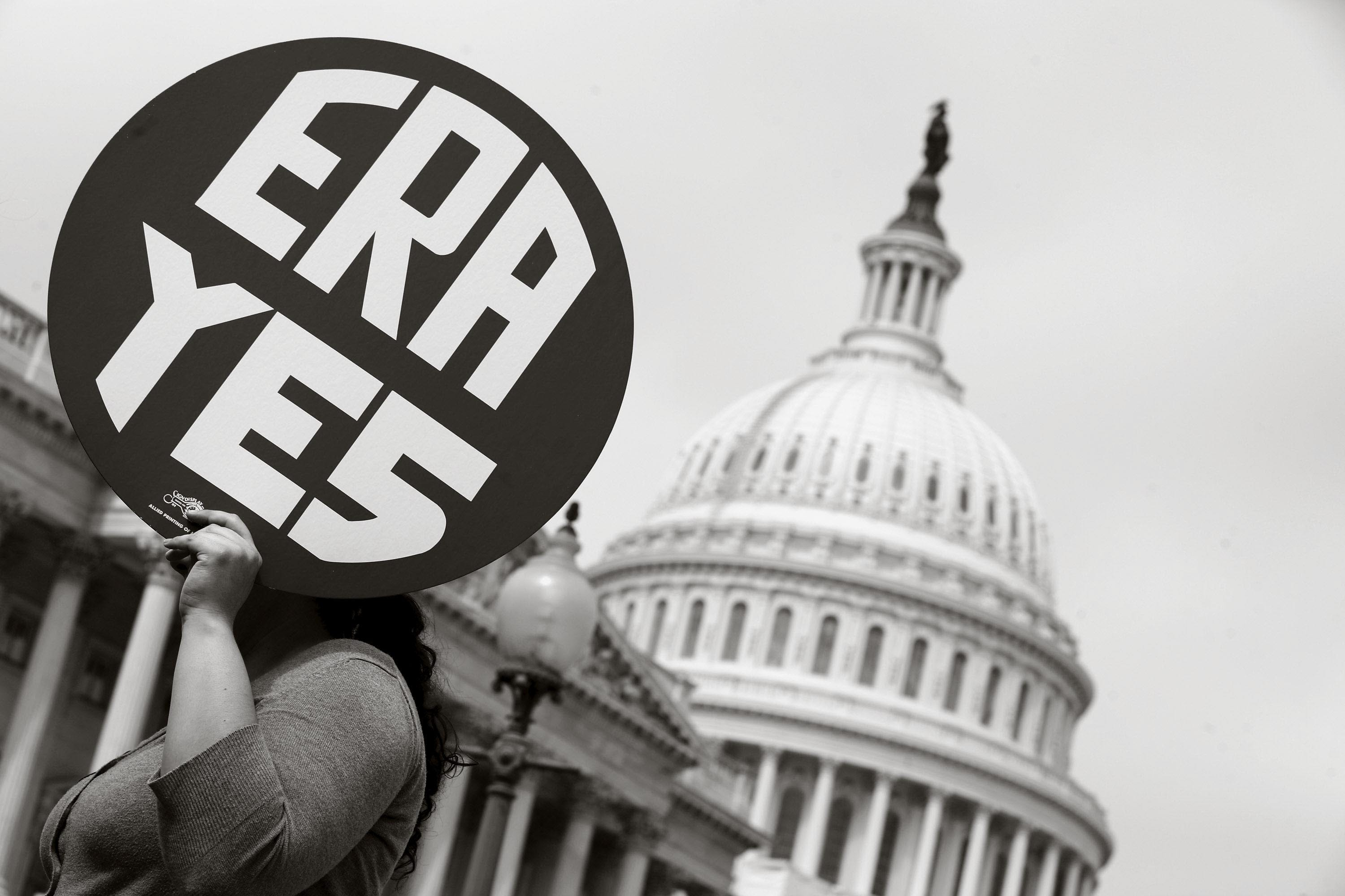 A woman holds up a sign as members of Congress and representatives of women's groups hold a rally to mark the 40th anniversary of congressional passage of the Equal Rights Amendment (ERA) outside the U.S. Capitol March 22, 2012, in Washington, D.C.