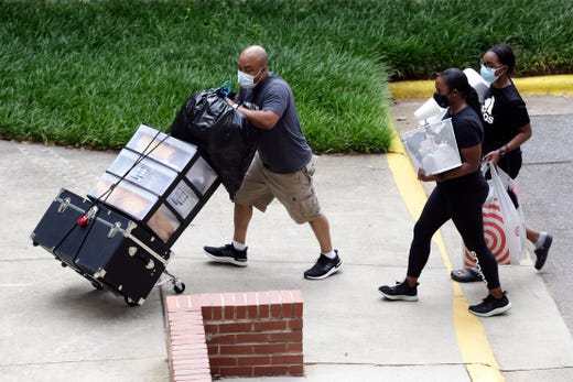 College students with the assistance of family begin moving in for the fall semester at N.C. State University in Raleigh, N.C., July 31, 2020. The first wave of college students returning to their dorms arenÕt finding the typical mobs of students and parents. At N.C. State, the return of students was staggered over 10 days and students were greeted by socially distant volunteers donning masks and face shields.