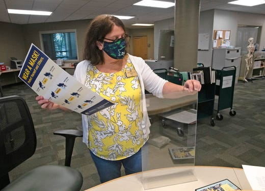 Pensacola State College Librarian Dena Gilliam prepares for the return of students by putting out COVID-19 reminders on Aug. 12, 2020 in Pensacola, Fla..
