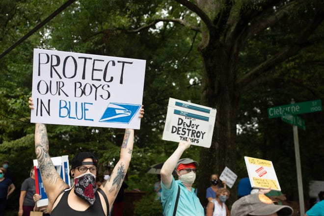 A group of protestors hold a demonstration in front of Postmaster General Louis DeJoy's home in Greensboro, North Carolina on August 16, 2020.