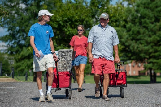 Baylor Garland, left, arrives to move in for his freshman year, assisted by his father Alan, right and mother, Teena, after they arrived from Eaton, Ga., at the University of Alabama on Aug. 15, 2020, in Tuscaloosa, Ala. More than 20,000 students returned to campus for the first time since spring break with numerous school and city codes in effect to limit the spread of COVID-19.