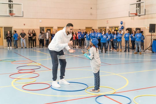 Ben Simmons works with a student during a community event.