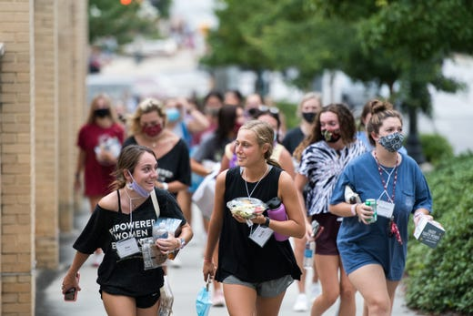 College students walk carrying their dinners at the University of South Carolina on Aug. 10, 2020 in Columbia, S.C.. Students began moving back to campus housing Aug. 9 with classes to start Aug. 20.
