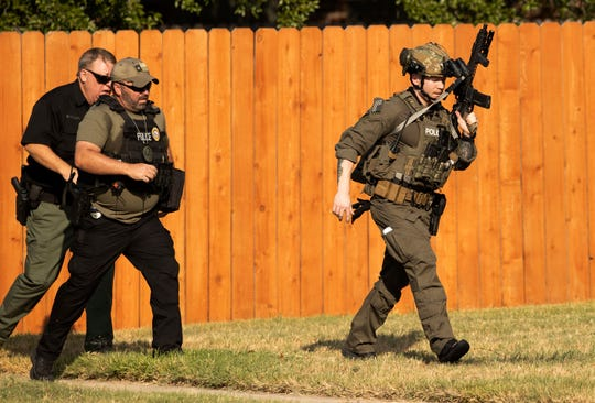 Police officers work near the house in Cedar Park, Texas, where a person remained barricaded Sunday, Aug. 16, 2020. Three police officers were shot, authorities said. The officers are in stable condition at a local hospital, police said on Twitter. (Jay Janner/Austin American-Statesman via AP) ORG XMIT: TXAUS321