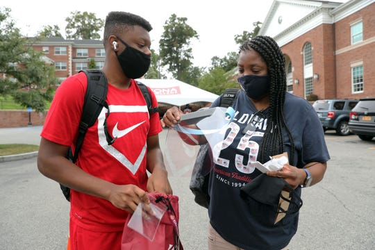 Sophomore Brandon Williams of the Bronx and his mother, Julie Andrew, look at a welcome bag which included a face mask, hand sanitizer and a face shield at Iona College in New Rochelle, N.Y., on Aug. 13.