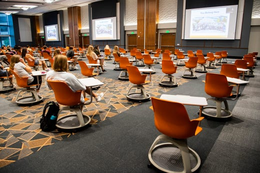 Students sit in socially distanced desks in a ballroom made into a classroom inside the Student Union at the University of Tennessee in Knoxville, Tenn. on Aug. 14, 2020.