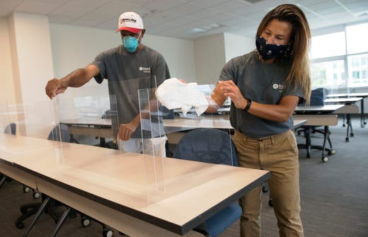 Groundskeeper Carrie Ward, right, and maintenance mechanic Samuel Francis adjust and disinfect a plexiglass divider, used to help prevent the spread of Covid-19, in a classroom of the TEC buildng at Rowan College on July 31, 2020 at Burlington County in Mount Laurel, N.J..