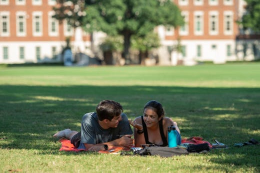 Matthew Claflin and Sara Norton sit in partial shade on the quad at the University of Alabama on Aug. 15, 2020, in Tuscaloosa, Ala.