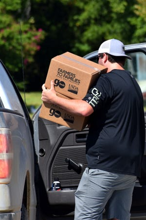 A volunteer with Impact Ardmore loads a vehicle with boxes of food at Dickson High School. The nationwide Farmers to Families meal box program has provided free food locally since June.