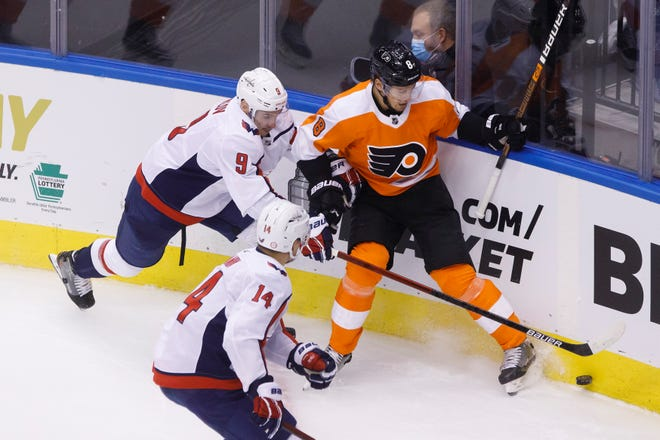 The Flyers' Robert Hagg and Capitals defenseman Dmitry Orlov battle for the puck. [Cole Burston/AP Photo]