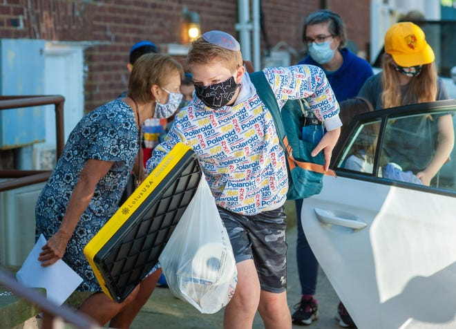 Lev Zilberberg of Yardley carries supplies as he heads into Abrams Hebrew Academy in Yardley Tuesday on students' first day back in classrooms in more than five months.