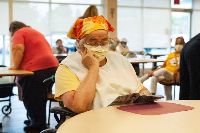 Mary Eckhardt reads a book in the cafeteria area before lunch at LIFE Beaver County's center, 131 Pleasant Drive, Center Township.
