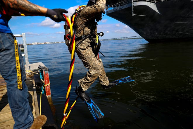 Jason Dayhuff, a student with the International Diving Institute in North Charleston, dives to work on a vessel at Patriots Point Naval & Maritime Museum in Mount Pleasant on Aug. 7.
