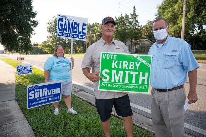 Jennifer Brown, Butch Hendrick and Don Oliver wave signs outside a voting precinct in Eustis on Tuesday. [Cindy Peterson/Correspondent]