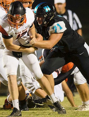 Oak Grove defensive lineman Nikolas Everhart tries to strip the football from North Davidson quarterback Landon Moore in a 2019 game. [Donnie Roberts/The Dispatch]